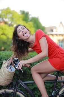 外国人 女性 ファッション 白人 モデル 20代 レディース 1人 一人 美人 美女 ロングヘア 黒髪 茶髪 屋外 野外 晴れ 晴天 自然体 公園 広場 自転車 乗る 乗っている 運転 自転車に乗る 座る 座っている カメラ目線 なびく 躍動感 全身 笑う 笑顔  舌を出す あっかんべー ふざける 楽しい mdff011