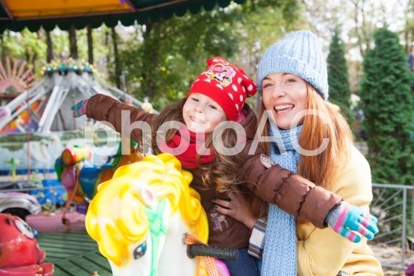 メリーゴーラウンドに乗る女の子とお母さん7の写真
