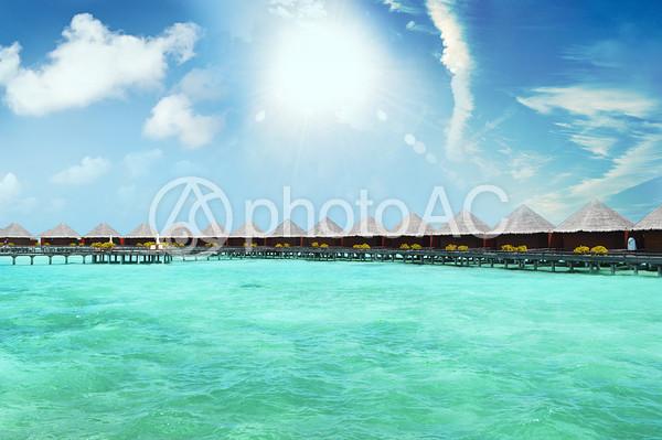 太陽の陽がふりそそぐ浅瀬の海と海上コテージの写真