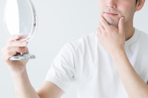 鏡を見る男性の写真