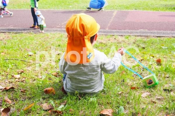 芝生の斜面に座る子供の写真
