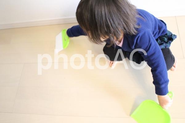 ほうきとちりとりで掃除する子供2の写真