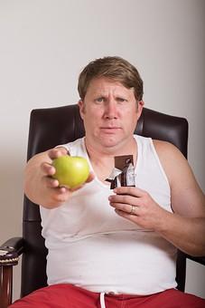 チョコレート 板チョコ  お菓子 スナック 間食 おやつ 高カロリー 青林檎 青リンゴ 青りんご 果物 ダイエット 食べたい 衝動 葛藤 外国人 男性 肥満 メタボ 茶髪 ブロンド 中高年 40代 デブ ぽっちゃり 白 タンクトップ 上半身 選ぶ 白背景 白バック mdjms014