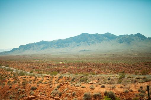 自然 植物 空 青空 晴天 晴れ 天気 青い グラデーション 山 山並み 山脈 荒地 崖 岩 茶色 岩肌 険しい 危険 木 樹木 葉 葉っぱ 緑 土 地面 広い 広大 雄大 屋外 室外 風景 景色 アメリカ 外国 道路