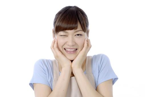 人物 屋内 白バック 白背景 日本人 1人 女性 20代 30代 エプロン  奥さん 奥様 婦人 家庭人 夫人 主婦 若い  ポーズ 顔 頬 表情  手 両手 載せる のせる  片目 目 つむる 瞑る ウインク 瞬き まばたき 目つき 失敗 ごまかす mdjf018