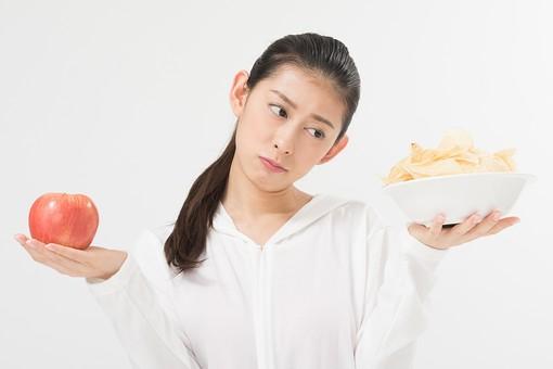 日本人 女性 美容 ダイエット モデル 一人 黒髪 美白 スタジオ撮影 背景白 背景なし 背景無し 白壁 綺麗 美人 髪アップ ポニーテール アップスタイル ナチュラルメイク 20代 30代 アラサー ボディー 細身 モデル体型 理想 体 エステ ビューティー 健康 痩せる シャツ りんご リンゴ 果物 フルーツ アップル ポテトチップス お菓子 おかし スナック 食べ物 おやつ 食事 比較 比べる カロリー 上半身 目線外し 悩む 白バック 白背景 mdjf011