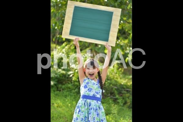 無地の黒板を持つ女の子の写真