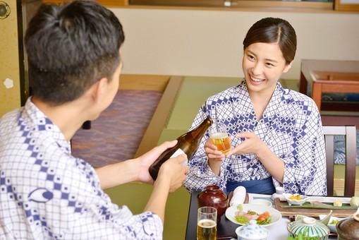 屋内 人物 日本人 2人  1人 大人 男性 女性  20代 30代 夫婦 カップル 温泉施設 宿泊施設 ホテル 旅館 旅行 温泉 浴衣 ゆかた 和服 食事 飲食 食べ物 日本料理 和食 料理 座卓 ビール 持つ 座る 飲物 和室 畳 和風 どうぞ 注ぐ 手を添える 見る 見つめる  グラス ありがとう ついでもらう 笑顔 微笑む お酌 mdjm001 mdjf013