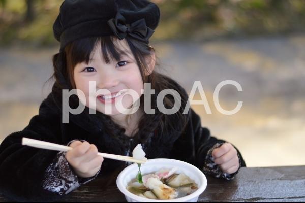 お雑煮を食べる子どもの写真