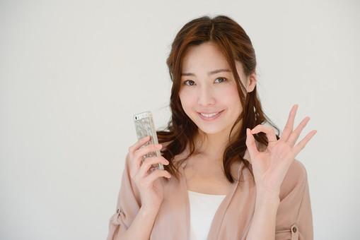 日本人 女性 女 30代 アラサー グレーバック 背景 グレー ポーズ ハーフアップ 髪型 茶髪 ナチュラル 私服 カジュアル ピンク ピンクベージュ 電話 携帯 携帯電話 スマホ スマートホン 笑顔 スマイル サイン ジェスチャー OK OKサイン mdjf013