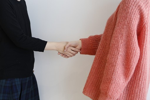 人物  ビジネス 会社 社員 会社員 2人 女性 OL 屋内 白バック 白背景 手 握手 向き合う ボディーパーツ 部分 アップ 協力 仲直り 自己紹介 挨拶 共同 連携 手を組む 駆け引き