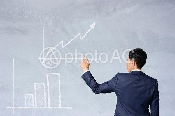 グラフを指し示すスーツの男性の写真