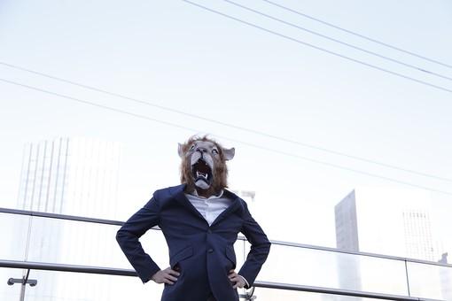 動物 動物マスク 人物 人間 ビジネス 会社 社員 会社員 社長 ビジネスマン 男性 1人 ライオン 腰に手を当てる 威張る 仁王立ち ふんぞり返る 偉い 立つ 屋外 空 青空 ビル オフィス 街並み 堂々たる