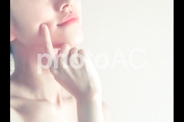 頰を指差す女性の写真