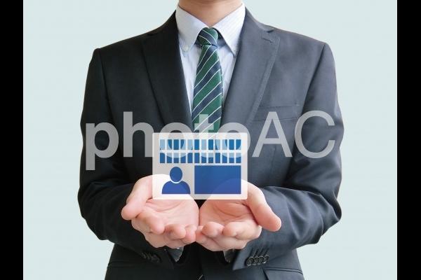 マイナンバーカードを手にするビジネスマンの写真