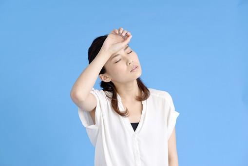 女性 ポーズ 人物 30代 日本人 黒髪 爽やか カジュアル 屋内 正面 ブルーバック 青背景 半そで 白  片手 左手 上半身 痛い 頭 手を当てる 我慢 頭痛 痛み 首 曲げる 疲労 疲れる 目 瞑る 憂鬱 不安 気が抜ける 熱 発熱 風邪 mdjf013