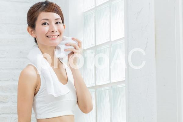 汗を拭くスポーツウーマンの写真