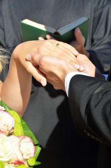 人物 外国人 新郎 新婦 花婿 花嫁 男性 女性 男の人 女の人 成人 男女 カップル 新婚 アベック 夫婦 夫 妻 ブーケ 花束 神父 聖書 ポーズ 手を取る 指輪 指輪の交換 マリッジリング 金 儀式 嵌める 手 指 幸せ 結婚式