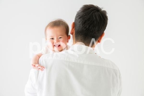 男性に抱かれる赤ちゃん(笑顔)の写真