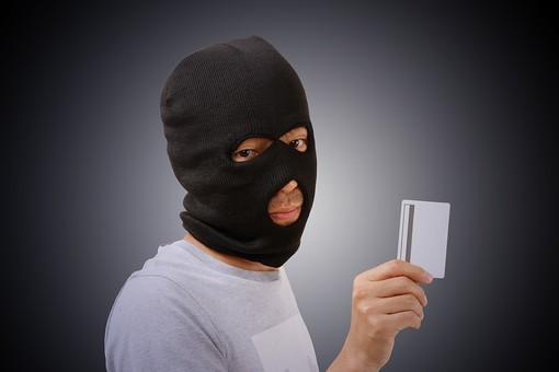 人物 男性 犯罪 犯罪者 犯行 犯人 覆面 マスク カード クレジットカード キャッシュカード 詐欺 盗難 窃盗 泥棒 スリ クレジットカード犯罪 カード犯罪 スキミング フィッシング 不正使用 偽造 悪質 屋内 黒バック 黒背景 目出し帽 振込詐欺