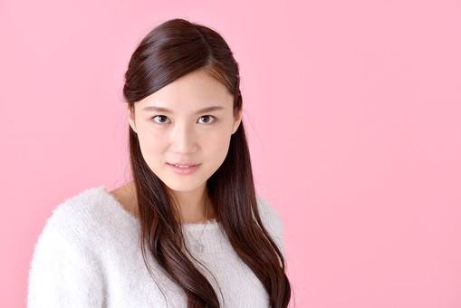 人物 女性 日本人 若者 若い   20代 美人 かわいい ロングヘア カジュアル  ラフ 私服 セーター ニット 屋内  スタジオ撮影 背景 ピンク ピンクバック ポーズ  おすすめ 上半身 正面 見つめる 真剣 険しい 表情 mdjf007