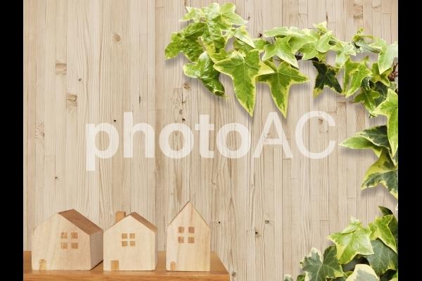 家の積木と木目テクスチャ背景と観葉植物の写真