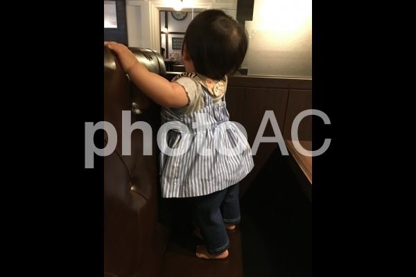 つかまり立ちする女の子 後ろ姿の写真