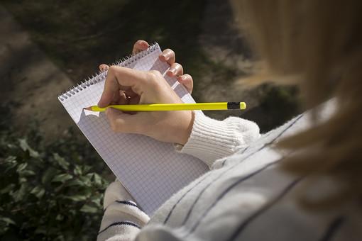 学生 記者 ライター 鉛筆 ペンシル 黄色 イエロー 消しゴム ノート 方眼 マス目 ページ リング 取材 記録 スケッチ レポート 筆記 メモ 書く 描く 記す まとめる 持つ 握る 執筆 右手 左手 右利き 庭先 ガーデン 屋外 野外 日光