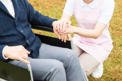 老人 高齢者 お年寄り シニア 男性 男 おとこ  2人 二人 白衣 エプロン ピンク  介護士 看護師 エプロン  散歩 外出 介護 不自由 椅子 ヘルパー 屋外 緑 木々 木 ジャケット ズボン 青  車いす 車椅子    座る  握る 手 両手