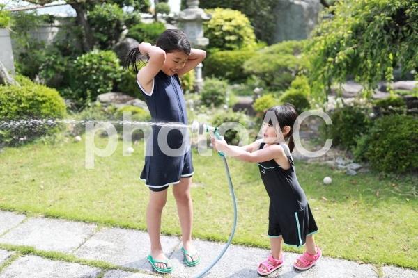 水遊びをする姉妹の写真