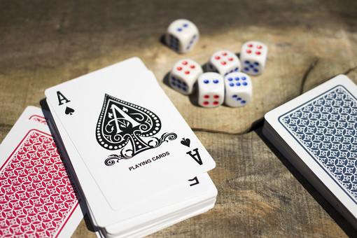 トランプ カード ゲーム 札 娯楽 木 屋外 茶色 机 テーブル 赤 青 裏側 裏 絵札 黒 木目 手品 マジック 遊び 絵札 乱雑 サイコロ  重ねる 配る 切る カードゲーム エース 1 A スペード