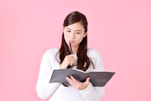 人物 女性 日本人 若者 若い  20代 美人 かわいい ロングヘア カジュアル  ラフ 私服 セーター ニット 屋内  スタジオ撮影 背景 ピンク ピンクバック ポーズ  おすすめ ファイル ノート 考える 勉強 疑問 問題 上半身 mdjf007