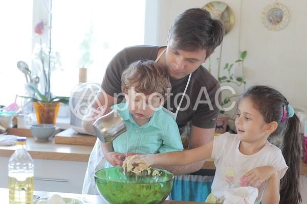台所で料理の手伝いをする子供たちと父親3の写真