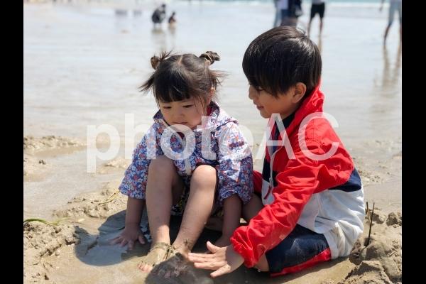 砂遊びをする兄弟の写真