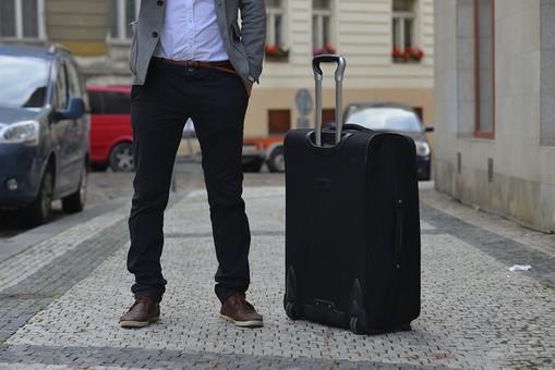 外国人 男性 旅行 人物 キャリーケース 海外 チノパン 旅 トラベル シャツ ジャケット 石畳 車 カジュアル 町 街 歩く 観光 出張 屋外 古い町並み 道 外国 下半身 立ち 正面 黒 ブラック グレー パンツ ズボン 一人 ポケット 手を入れる
