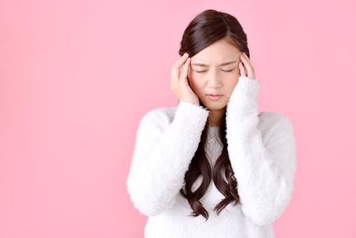人物 女性 日本人 若者 若い  20代 美人 かわいい ロングヘア カジュアル  ラフ 私服 セーター ニット 屋内  スタジオ撮影 背景 ピンク ピンクバック ポーズ  おすすめ 上半身 悩む 考える 困る 困惑 迷う 頭痛 頭 痛い 集中 mdjf007
