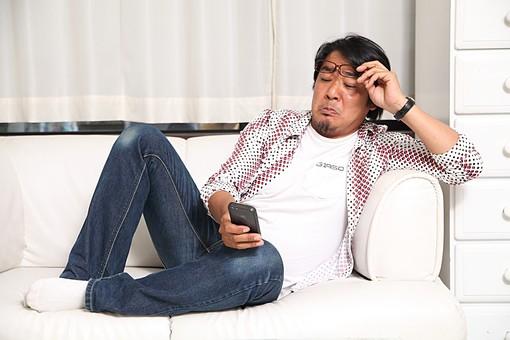 人物 日本人 男性 中年 40代 1人 部屋 室内 屋内 リビング ソファ 電話 携帯 スマホ スマートフォン 寝そべる 寛ぐ くつろぐ リラックス 老眼 見にくい 文字 眼鏡 外す 加齢 休日 オーバーリアクション mdjm010