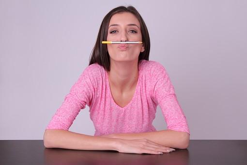 人物 女性 外国人 外人 外国人女性 外人女性 20代 30代 ロングヘア 上半身 屋内 室内 スタジオ撮影 白バック 退屈 暇 飽きる 無気力 机 肘をつく 鉛筆 鼻 挟む ユーモア ユーモラス 正面 勉強 ペン  mdff056