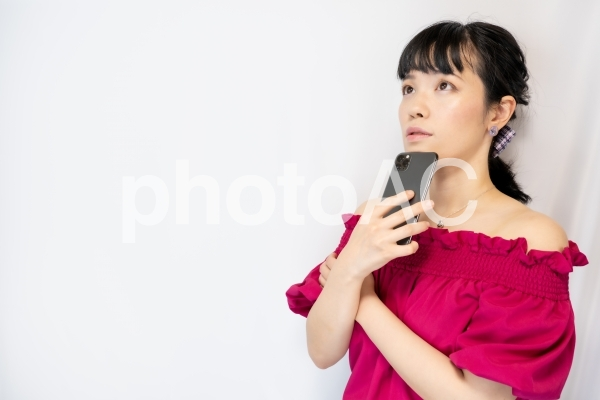 スマホを持って考える女性(白背景)の写真