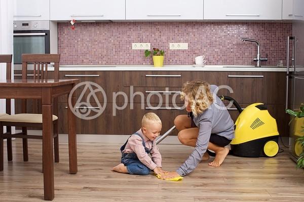 掃除の真似をする息子と掃除機をかけるワーキングマザー2の写真