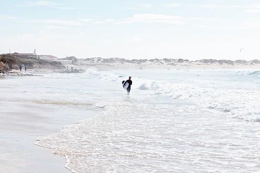 リゾート 自然 風景 スポーツ 人物 1人 アウトドア サーフィン サーフボード サーファー   ウェット ドライスーツ ラッシュガード マリンスポーツ レジャー 遊び   海 波 白波 海岸 波打ち際 砂 砂浜 ビーチ  水際 曇り 空 雲 夏 歩く 洋館 建物  全身   外国 海外