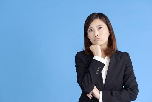 人物 女性 日本人 20代 若者  ビジネス スーツ 黒 紺色 セミロング  OL 社会人 会社員 ビジネスマン 就活  就職活動 真面目 ポーズ 屋内 スタジオ撮影  ブルーバック 上半身 頬杖 困る 困った 悩む 考える 疑問 首を傾げる わからない コピースペース mdjf013