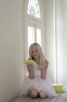 人物 外国人 外人 こども 子供  子ども 女の子 少女 キッズモデル ポートレート  かわいい キュート 無邪気 あどけない 長髪  ロングヘア 金髪 ブロンド ストレートヘア 屋内 室内 部屋 ベッド ソファ ファッション ドレス ワンピース 白 窓辺 座る 正座 本 読書 読む 笑顔 スマイル ポーズ ポートレイト mdfk012