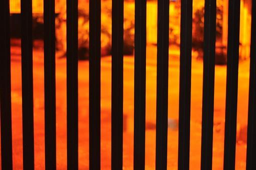 柵 フェンス 檻 囲い 境界 仕切り 縦じま 縞模様 ストライプ 筋 棒 配列 順番 シルエット 黒 ブラック 橙色 オレンジ 灯り 明かり 抽象的 デザイン 背景ボケ ボケ味 フィリピン 海外 外国 異国