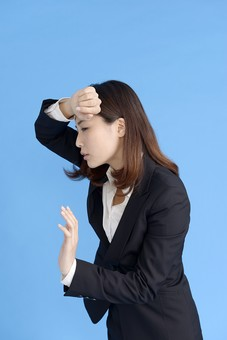 人物 女性 日本人 20代 若者  ビジネス スーツ 黒 紺色 セミロング  OL 社会人 会社員 ビジネスマン 就活  就職活動 真面目 ポーズ 屋内 スタジオ撮影  ブルーバック 上半身 横向き 額 押さえる 体調不良 貧血 めまい  mdjf013
