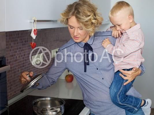 キッチンで息子を抱っこしながら家事をするお母さん6の写真