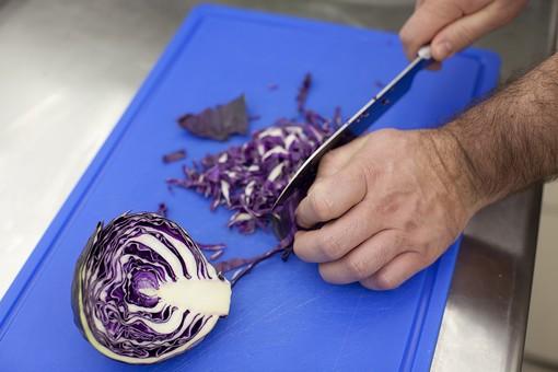 厨房 台所 キッチン 料理 調理  コック シェフ 料理人 包丁 ナイフ 切る カット まな板 レストラン 仕込み 下準備 野菜 青 バット ボディパーツ 腕 持つ 手 紫キャベツ レッドキャベツ 赤きゃべつ  千切り 細かい 細かく 男性 外国人