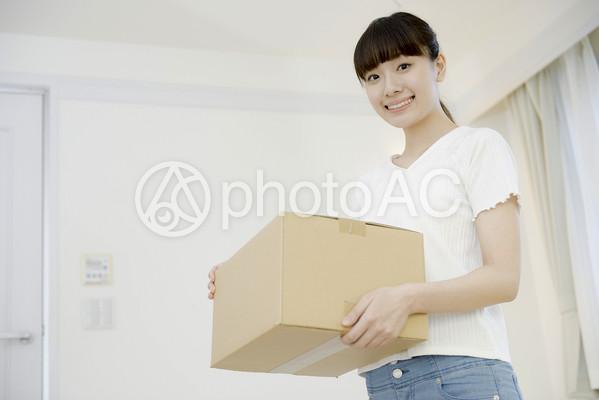 引越し作業中に段ボール箱を持って立つ女性6の写真