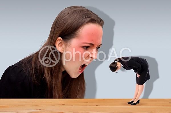 大きな人に怒られる女性の写真
