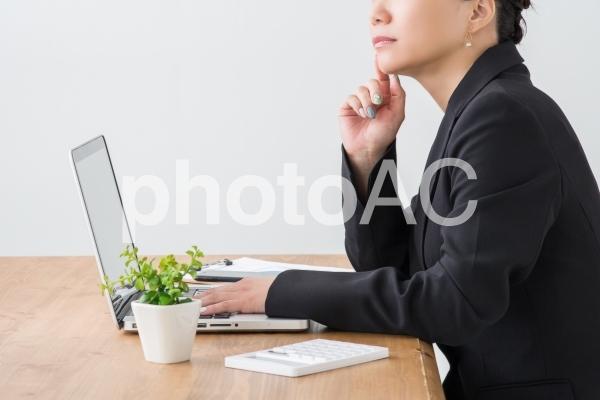デスクで考える女性の写真